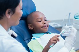 stock photo of false teeth  - Female dentist teaching boy how to brush teeth in the dentists chair - JPG