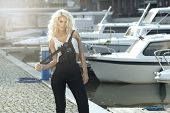 picture of marina  - Stylish woman in dungarees standing on marina - JPG