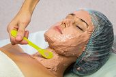 foto of facials  - Beautiful woman with facial mask at beauty salon - JPG
