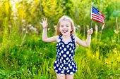 pic of long tongue  - Funny little girl with long curly blond hair putting out her tongue and waving american flag outdoor portrait on sunny day in summer park - JPG