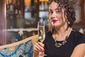 picture of champagne glass  - Beautiful young brunette woman drinking champagne - JPG