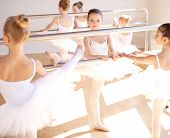 stock photo of ballet barre  - Group of pretty young girls in white tutus in a class at the ballet school training at the bar practicing their positions focus to a ballerina in the centre - JPG