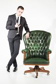 pic of prosperity  - Male businessman sitting on a green leather chair on a white background - JPG