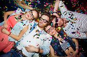 stock photo of slumber party  - Young friends sleeping in confetti on the floor in nightclub after party - JPG