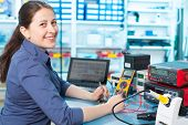picture of circuits  - Woman with a tester and a printed circuit board - JPG
