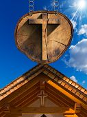 picture of mountain chain  - Wooden Christian cross on a section of tree trunk hanging from a metal chain - JPG