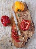 image of pepper  - Red and yellow peppers sliced red peppers on olive wood board and vintage knife - JPG