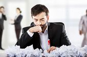 picture of thoughtfulness  - Thoughtful businessman with crushed paper sheets - JPG