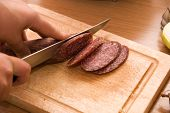stock photo of hand cut  - Hand closeup cuts salami with slice pieces at table - JPG