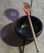 foto of slit  - Wooden spoon skimmer highlighted in red with slits in the form of smiles and its ominous shadow on the old wooden dirty white floor - JPG