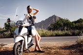 foto of scooter  - Beautiful young blonde girl traveling on scooter - JPG