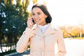 stock photo of girl walking away  - Cheerful woman talking on the phone outdoors and looking away - JPG