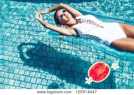 Girl floating on beach mattress and eating watermelon in the blue pool. Tropical fruit diet. Summer