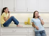 stock photo of tlingit  - Two teenage girls talking on cell phones - JPG