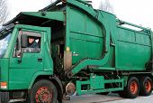 stock photo of trash truck  - old green garbage truck with driver on frost - JPG
