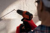 Close up construction workerâ??s hand using electric drill making hole in wall. Detail of bricklaye poster