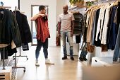Customer holds up clothes in a shop while assistant looks on poster