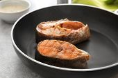 Tasty rainbow trout steaks on frying pan, closeup poster