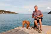 picture of epidavros  - man with his dog sitting in harbor - JPG