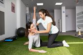 Physical Therapist Assisting Young Caucasian Woman With Exercise poster