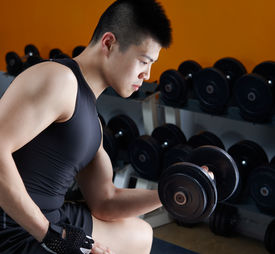 stock photo of lifting weight  - asian man working out in gym using dumbbell - JPG