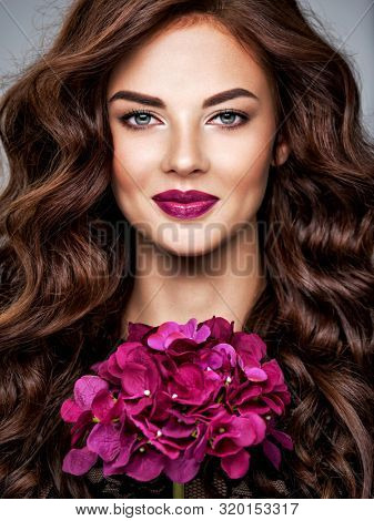 poster of Beautiful woman with long curly hair and bright purple make-up.  Young caucasian gorgeous adult girl