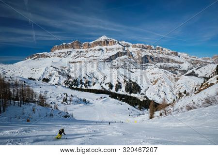 poster of View of a ski resort piste with people skiing in Dolomites in Italy. Ski area Arabba. Arabba, Italy