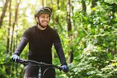 Joyful Male Bicyclist Cycling In Mountain Forest In Sun Flares, Enjoying The View, Copy Space poster