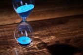 Time Passing, Deadline, Urgency Concept. Time Management. Blue Hourglass On Wooden Background. Copy  poster