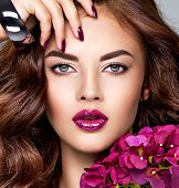 Beautiful  woman with purple make-up of lips and fingernails. Closeup womans portrait with flowers. poster