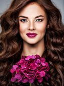 Beautiful woman with long curly hair and bright purple make-up.  Young caucasian gorgeous adult girl poster