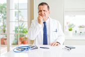Middle age doctor man wearing medical coat at the clinic looking stressed and nervous with hands on  poster