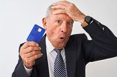 Senior grey-haired businessman holding credit card over isolated white background stressed with hand poster