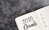 2020 On The Office Desk In A Notebook. Plans And Goals For The New Year. Top View Layout On White Ba poster