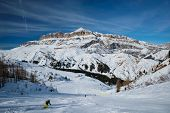 View of a ski resort piste with people skiing in Dolomites in Italy. Ski area Arabba. Arabba, Italy poster