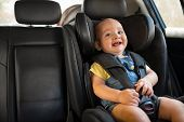 Portrait of happy little child sitting in car seat with safety belt, enjoying road trip. Cute baby b poster