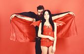 Man And Woman Dressed Like Vampire, Demon, Red Background. Vampire In Cloak Behind Sexy Devil Girl.  poster