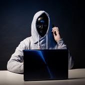 Anonymous Hacker In Mask Programmer Uses A Laptop And Talking On The Phone To Hack The System In The poster