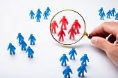 Hand Holding Magnifying Glass Over Red Human Figures Surround By Blue Human Figure Group poster