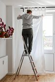 Woman Stands On A Stepladder Near The Window And Hangs White Curtains On The Curtain Rod poster