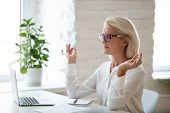 Calm Aged Woman Meditate With Mudra Hands In Office poster