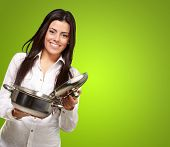 stock photo of saucepan  - portrait of a young girl opening a sauce pan over a green background - JPG