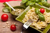stock photo of pesto sauce  - Italian Cuisine - First Courses - Pasta (farfalle) garnished with pesto sauce.