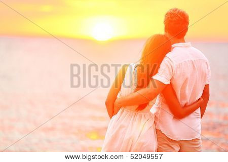 Honeymoon couple romantic in love at beach sunset. Newlywed happy young couple embracing enjoying oc poster