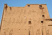 stock photo of isis  - First Pylon relief of the Temple of Edfu with images of Egyptian gods of Osiris Isis Horus Set Thoth in Egypt - JPG
