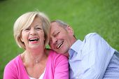 image of snuggle  - Happy attractive elderly couple laughing together as they snuggle affectionately while relaxing outdoors on the grass - JPG