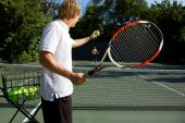 picture of post-teen  - Tennis Instructor Teaching His Student holding the ball to show him - JPG