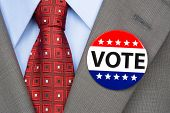 A voter wears a vote pin on his suit lapel during election season