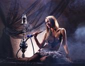 stock photo of hookah  - Young sexy woman in luxury underwear smoking the hookah in vintage interior - JPG