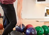 Midsection of young man choosing bowling ball from rack in club